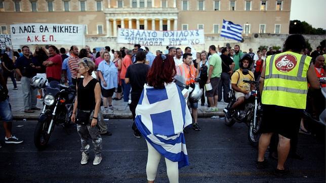 Una manifestante envuelta en la bandera griega participa en una protesta en frente del Parlamento Griego en Atenas