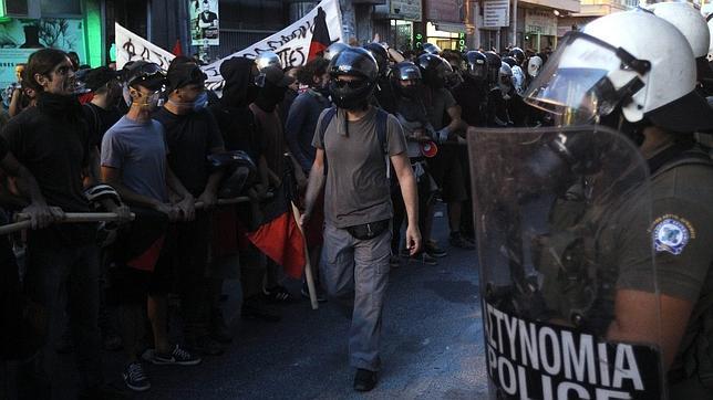 Manifestantes permanecen frente a policías antimotines durante una marcha contra el nazismo en Atenas
