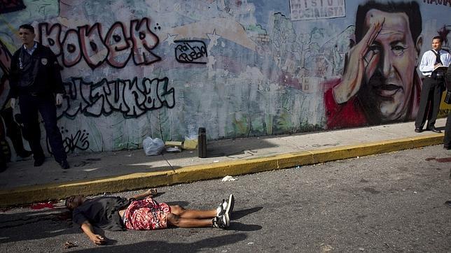 Un cadáver yace sobre el asfalto junto a un mural con la efigie de Hugo Chávez en una calle de Caracas, en una imagen de septiembre de 2010