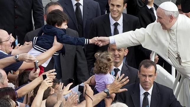 El Papa Francisco estrecha la mano a un niño a su llegada a la Plaza de San Pedro del Vaticano este miércoles