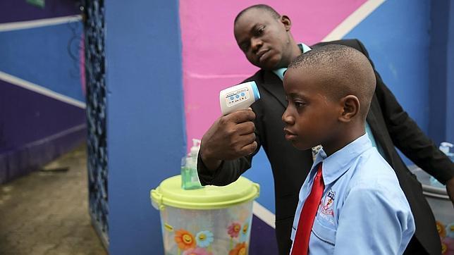 Un trabajador toma la temperatura a un estudiante usando un termómetro láser en una escuela