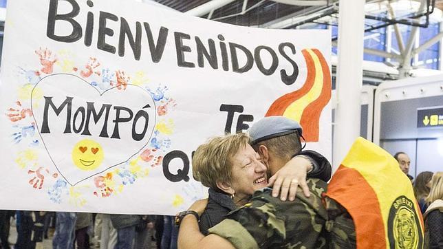 Un soldado se abraza al llegar al aeropuerto de Zaragoza, ante una pancarta de bienvenida