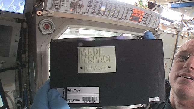 El comandante de la ISS Barry «Butch» sostiene el primer objeto hecho por una impresora 3D en el espacio