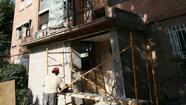 Un operario instala un ascensor exterior en un barrio madrileño