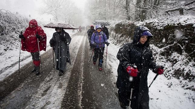 Peregrinos haciendo el camino de Santiago en pleno temporal