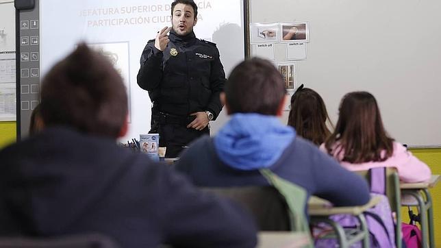 Un agente de la Unidad de Participación Ciudadana de la Policía Nacional imparte una charla a escolares de once años en un colegio de Madrid