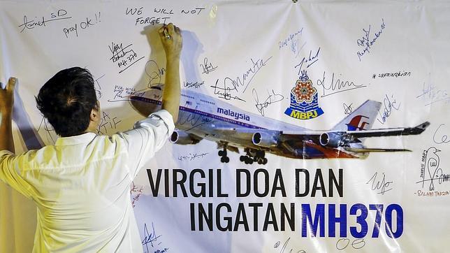 Un hombre escribe este viernes un mensaje durante un acto en recuerdo de las víctimas del vuelo MH370