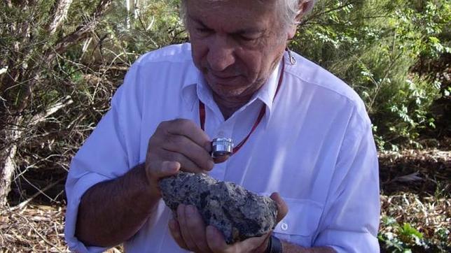 Andrew Glikson sostiene una muestra de suevita, una roca con material parcialmente fundido formada durante un impacto