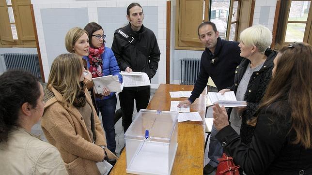 Los componentes de una mesa electoral en un colegio de Santiago de Compostela poco antes de la apertura al público