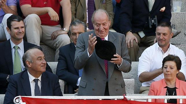 Don Juan Carlos, montera en mano tras recibir un brindis, junto a Fernando Benzo y Carmen del Riego