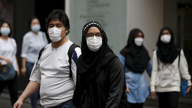 Turistas llevando mascarillas por miedo al contagio en las calles de Seúl