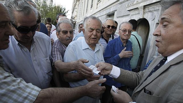 El empleado reparte turnos a un grupo de pensionistas frente a una sucursal del Banco Nacional de Grecia en el centro de Atenas