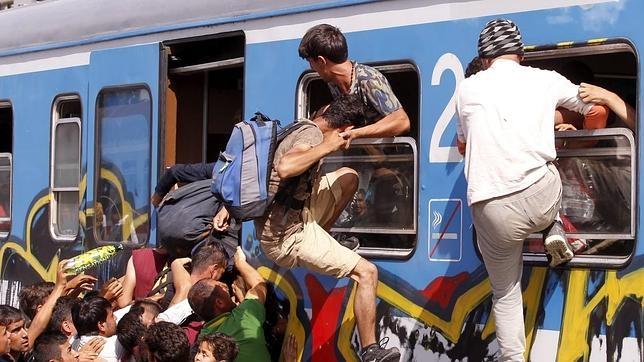 Refugiados se empujan entre sí para subir a bordo de un tren rumbo a Zagreb en la estación de Beli Manastir