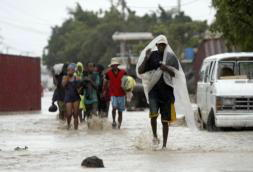 AP  Un grupo de residentes de Gonaives, en Haití, huye de sus casas en calles anegadas por las fuertes lluvias causadas por el paso del huracán «Ike»