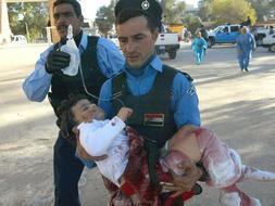 Dos policías trasladan en brazos a una niña herida en el atentado de Kirkuk./ Afp