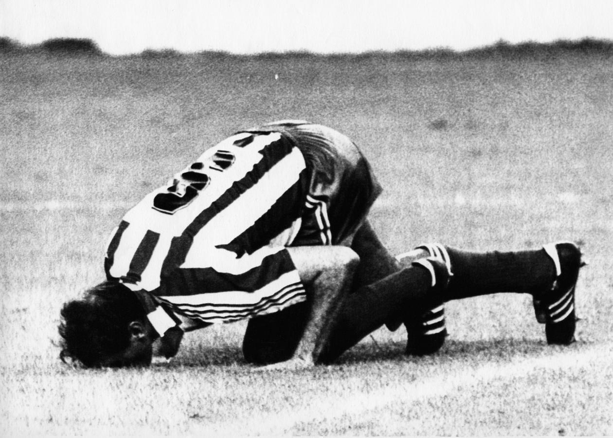 Quini besa el césped de El Molinón tras su partido de homenaje ante el Real Madrid, en 1987