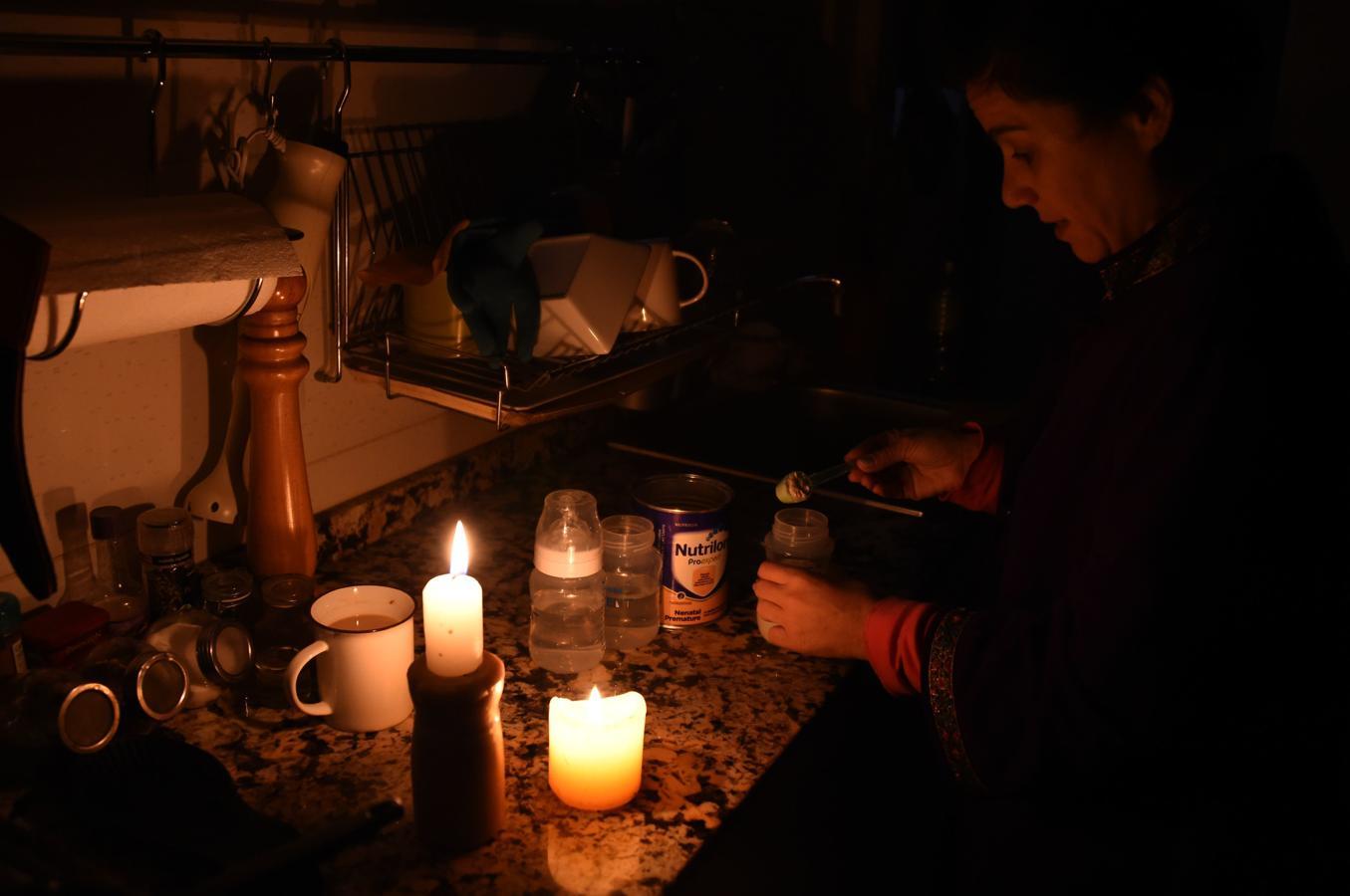 Una mujer prepara el biberón con velas en su casa en Montevideo