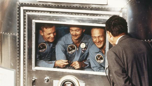 Nixon saluda a los tres astronautas del Apolo 11 en su cuarentena, tras su regreso a la Tierra