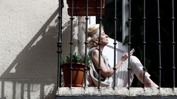 Una mujer toma el sol en su casa de Madrid durante el confinamiento