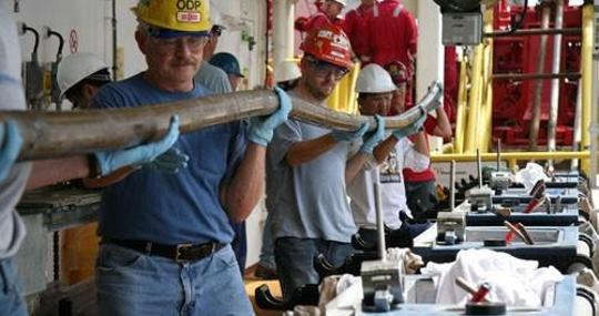 Investigadores portando un núcleo de sedimento