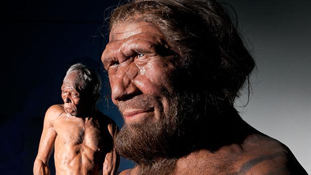 En primer plano, representación de un neandertal. Al fondo a la izquierda, un sapien