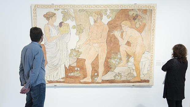 Dos personas contemplan «La Tierra, Eneas y Pan», un fresco que Torres-García pintó para la casa que se construyó en Tarrasa