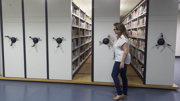 La bibliotecaria María Prego de Lis muestra los cinco compactos en los que están ubicados los alrededor de 25.000 volúmenes ya catalogados de la Biblioteca de Mujeres, en el Museo del Traje de Madrid
