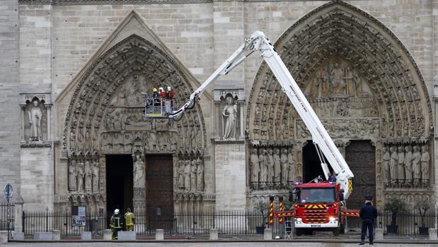 Varios bomberos trabajan en un elevador a la fachada de catedral de Notre Dame, este martes en París (Francia)