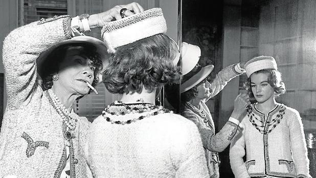 Coco Chanel, fotografiada mientras le prueba un traje a Romy Schneider