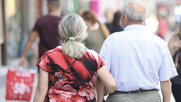 Un pareja de jubilados pasea del brazo por una calle de Madrid