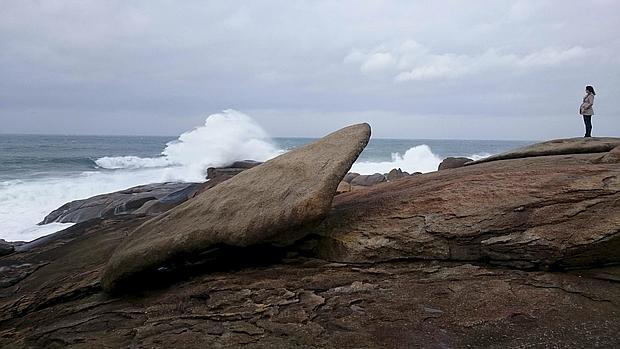 Una mujer contempla el Atlántico junto a la Pedra de Abalar, junto al santuario de la Virxe da Barca en Muxía