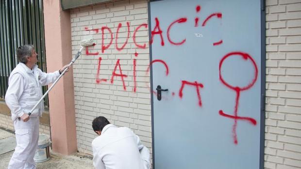 Los operarios limpian las paredes exteriores del templo con las pintadas