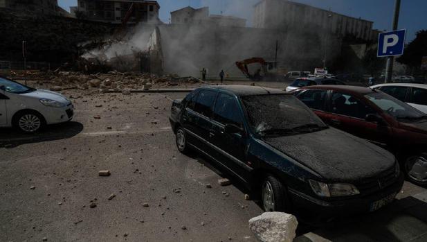 Los cascotes tras el derrumbe llegaron al otro lado de la calle mientras pasaban vehículos