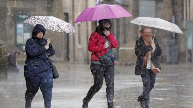 Tres mujeres se protegen de la lluvia durante la borrasca Ana