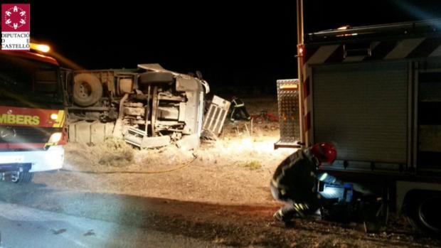El camión volcado y efectivos de Bomberos en el lugar del accidente mortal