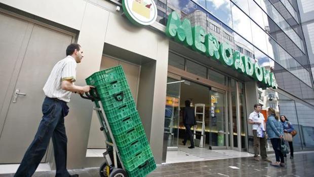 Imagen de un empleado de Mercadona frente a un supermercado de Mercadona en el centro de Valencia