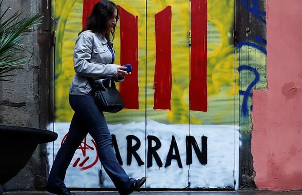 Una mujer pasa junto a una puerta pintada por Arran con una estelada