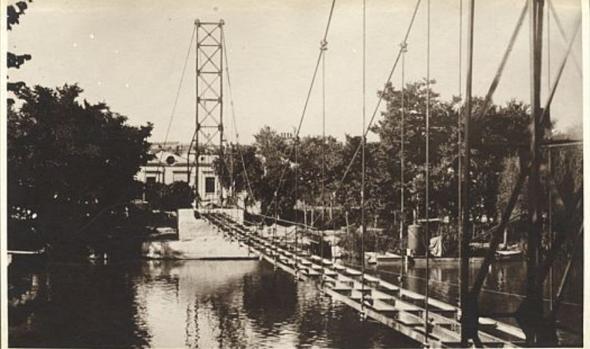 Pasarela colgante en construcción hacia 1925. Junto a la orilla, barca con la draga. Foto de José Vera. Archivo Municipal de Toledo