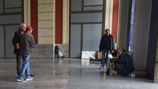 Un grupo de personas sin hogar en el vestíbulo de Príncipe Pio