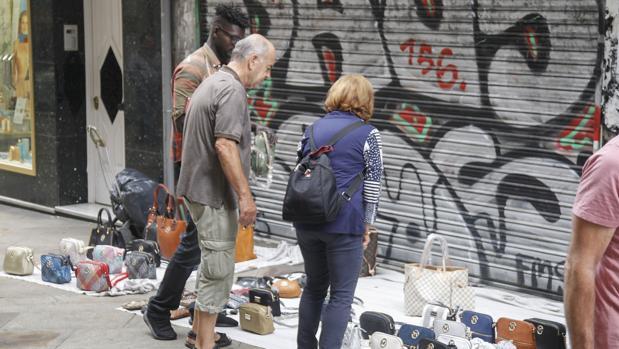 Uno de los manteros que frecuenta la calle Real de La Coruña, con una pareja que mira la mercancía