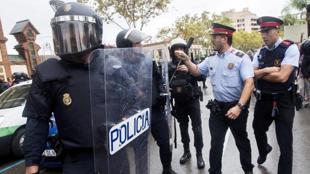 Agentes antidisturbios de la Policía Nacional y de los Mossos d' Esquadra discuten en Barcelona en el 1-O