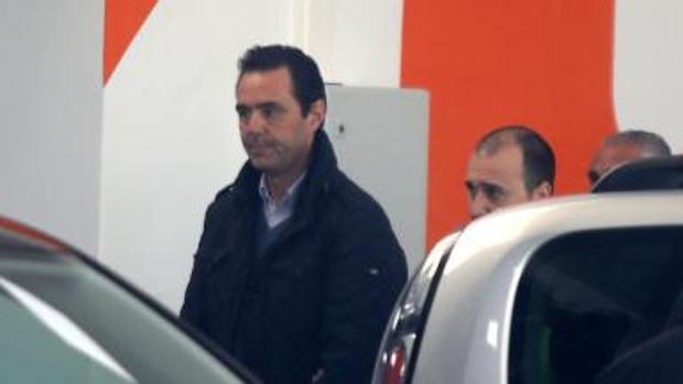Miguel López custodiado por policías en el lugar del crimen, el concesionario de coches que regentaba