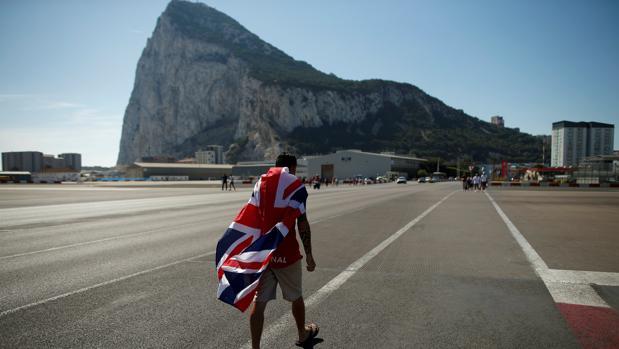 Un residente en Gibraltar camino por el aeropuerto con el Peñón de fondo