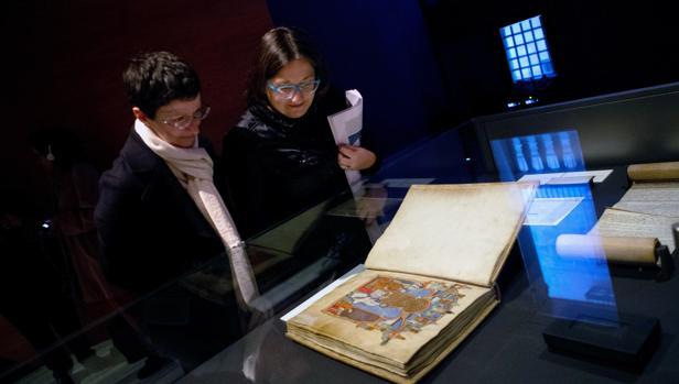 Dos visitantes observan el Gran Libro de los Feudos, un cartulario de documentos relativos a las relaciones feudales de los reyes de Aragón y condes de Barcelona