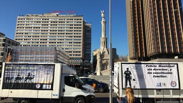 Los dos camiones reivindicativos de la Policía Municipal, ayer, a su paso por la plaza de Colón