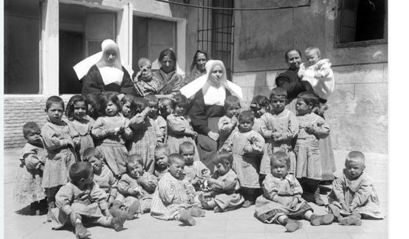 Grupo de niños con monjas y nodrizas en uno de los patios del Asilo (Fondo Santiago Relanzón. Archivo Municipal de Toledo)