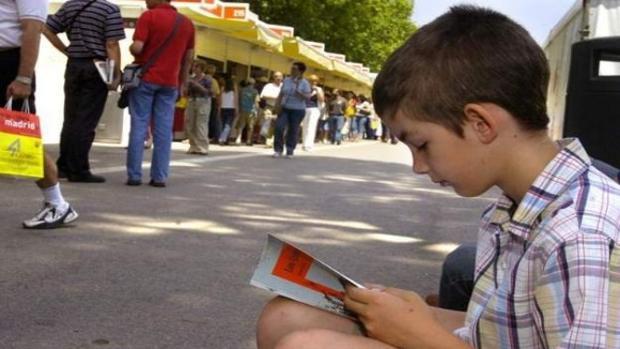 Un niño leyendo en la Feria del Libro