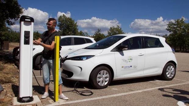 Un conductor recarga un coche eléctrico