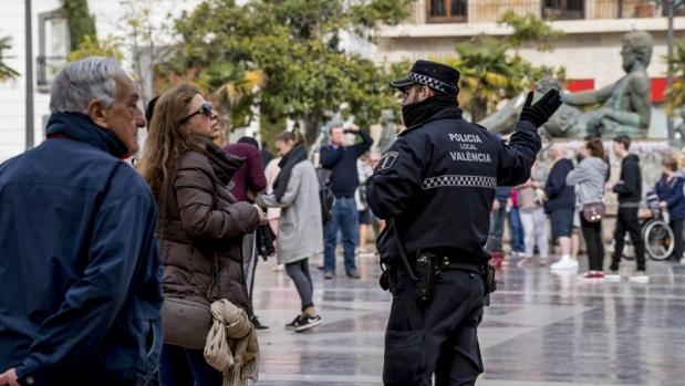 Un policía local habla con una mujer en la calle en Valencia