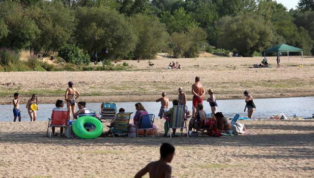 Un grupo de bañistas pasan una jornada de playa en Escalona